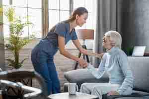 older woman shaking nurses hand