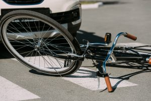 broken bicycle in front of a car
